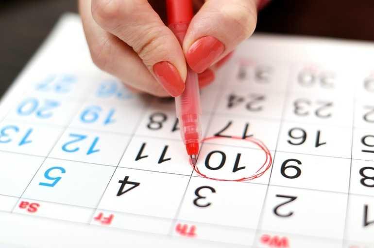 Женщина отмечает в календаре