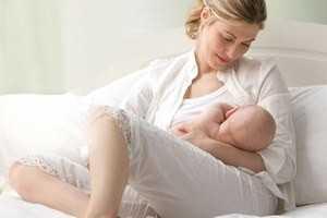 женщина держит ребенка у груди