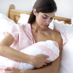женщина кормит ребенка грудным молоком