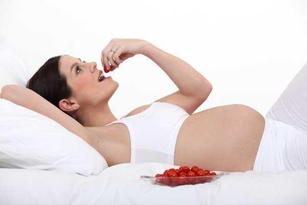 Беременная женщина кушает черешню