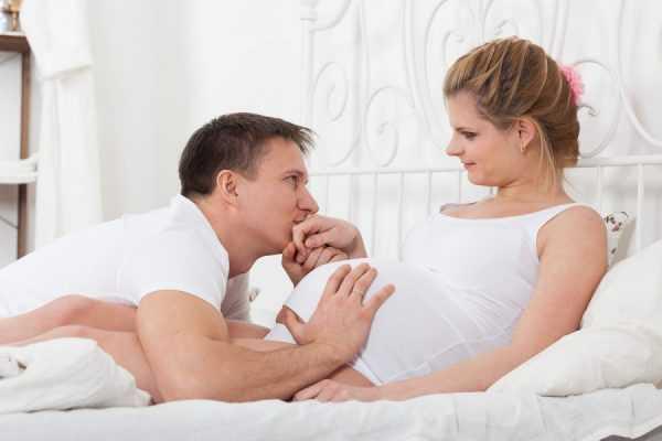Мужчина нежно целует руку беременной женщины и гладит её живот