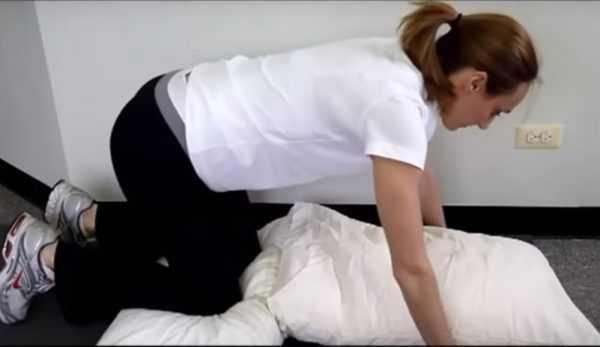 Женщина на четвереньках с подушкой под коленями