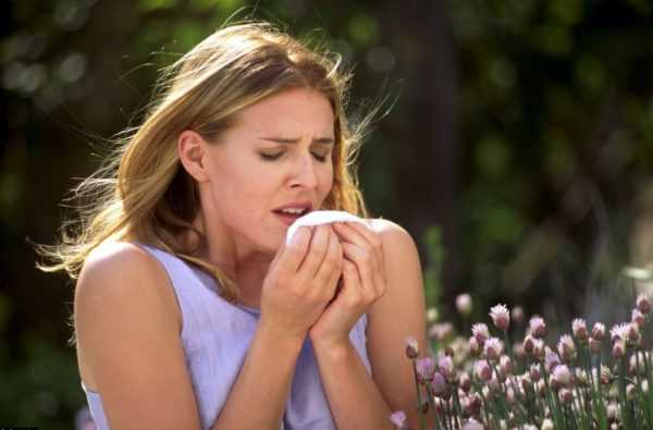 женщина рядом с цветами подносит платок к носу