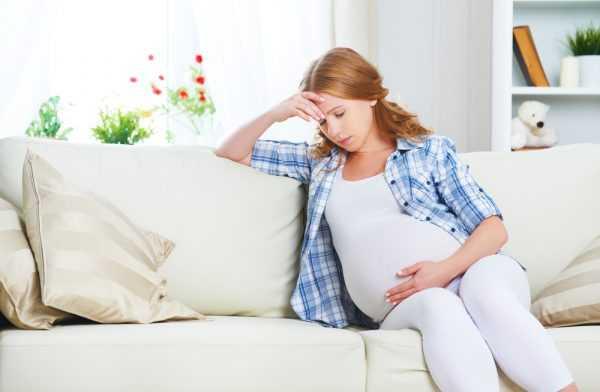 беременная сидит на диване, поддерживая рукой голову