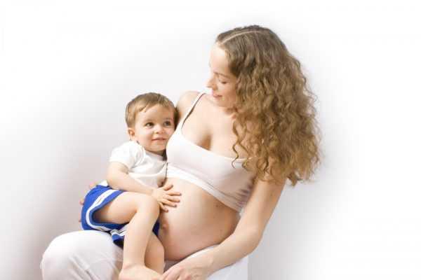 Беременная держит старшего ребёнка на руках