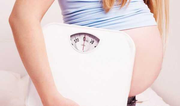 Беременная держит весы около своего живота