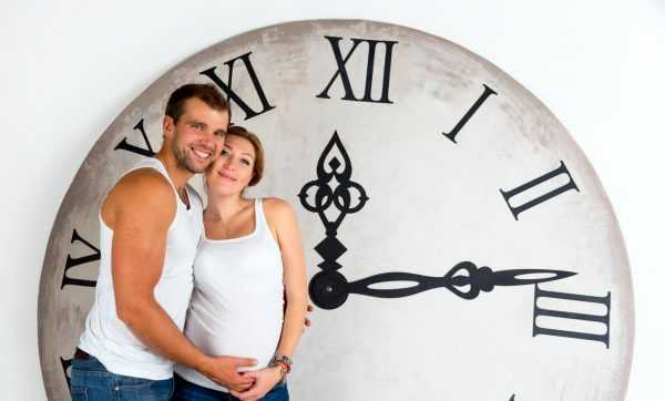 Беременная девушка с супругом у часов