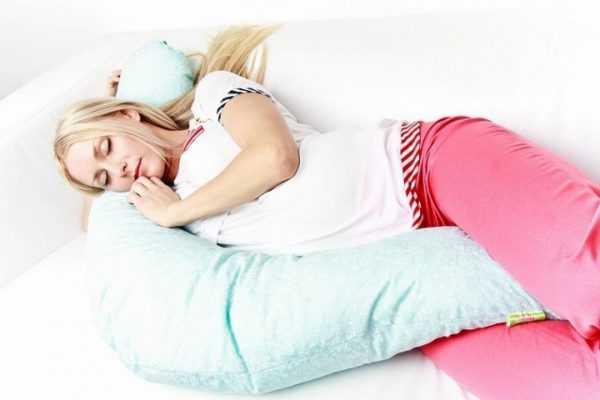 Беременная девушка спит на подушке для будущих мам