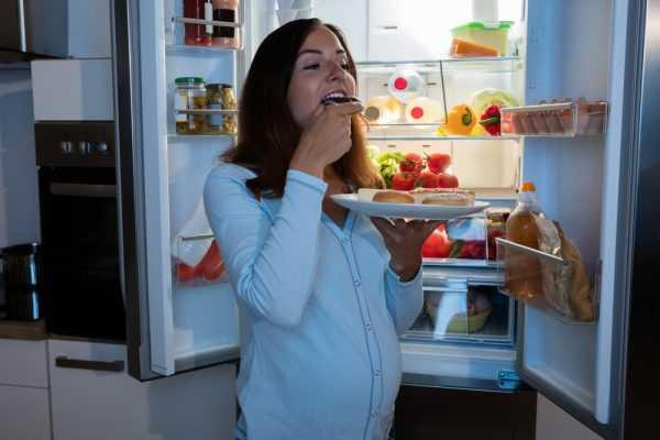беременная ест плюшки у открытого холодильника