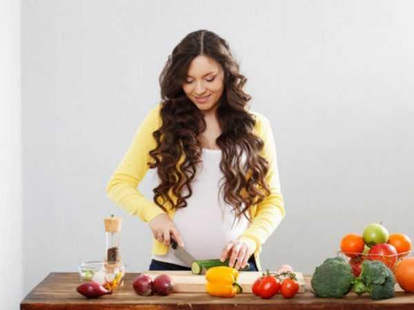 Беременная женщина режет огурец