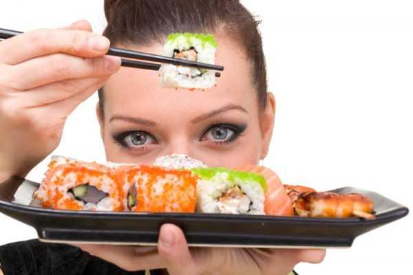 девушка держит в палочках суши