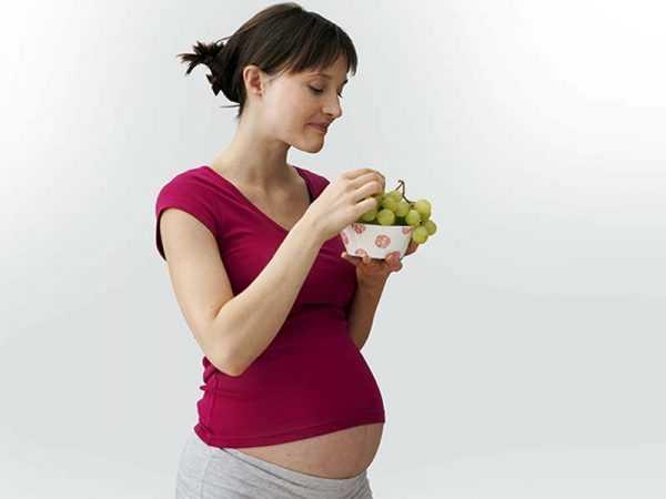 беременная держит чашку с виноградом