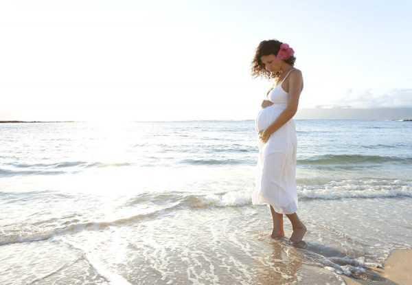 беременная гуляет по берегу моря