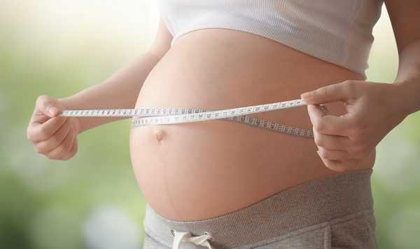 Беременная женщина измеряет живот