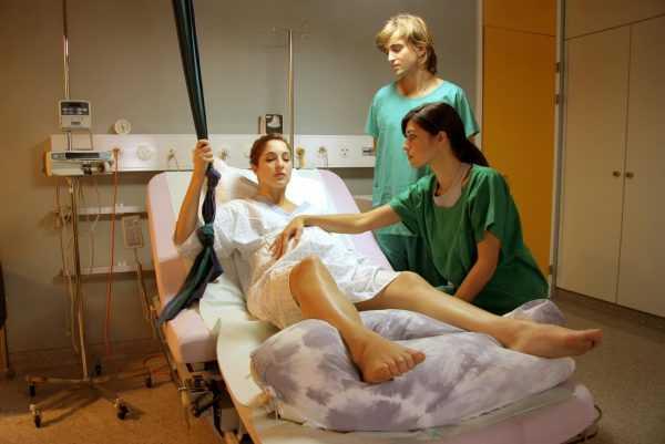 Беременная лежит со схватками в окружении медработников