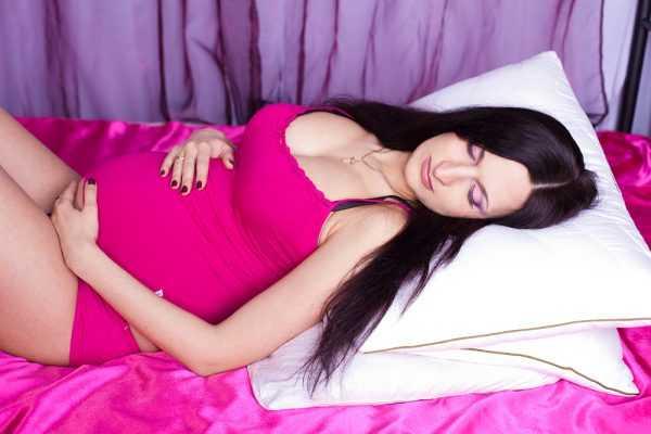 беременная лежит на кровати, закрыв глаза