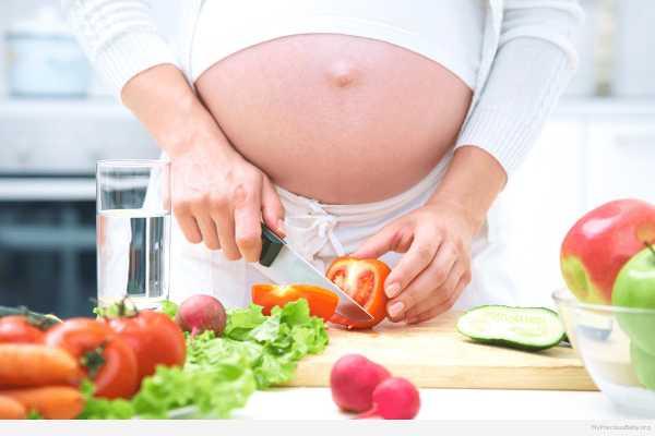 Беременная режет салат