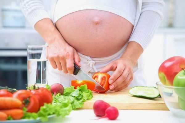 Беременная режет салат из свежих овощей