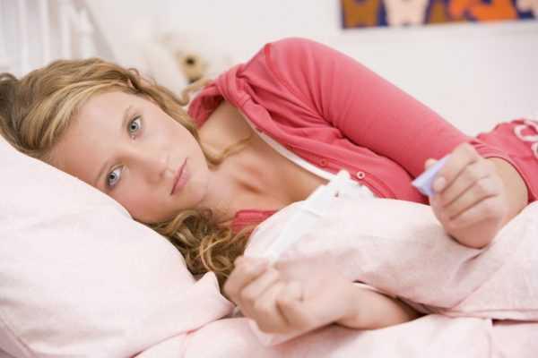 Беременная женщина лежит с градусником