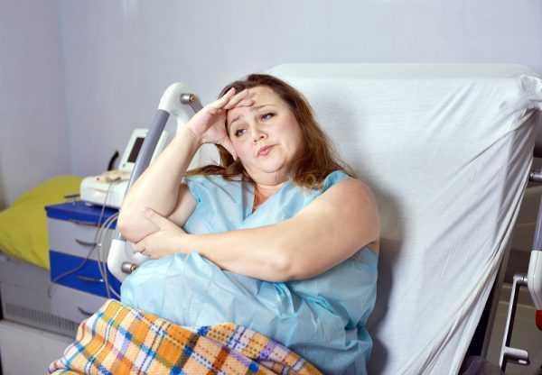 беременная с ожирением сидит на кровати