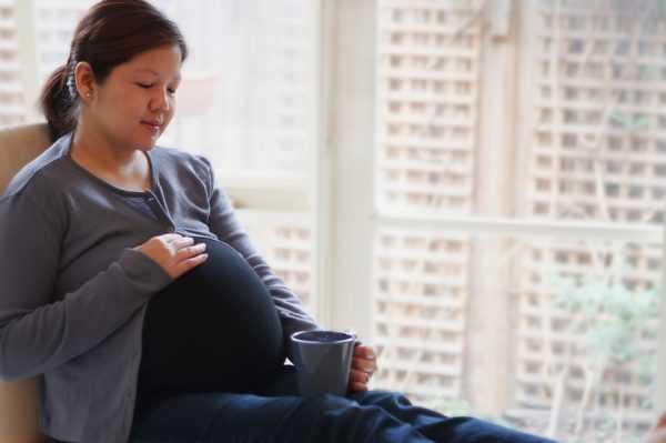 Беременная сидит и держит в руках кружку