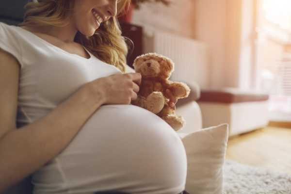 Беременная сидит с игрушкой в руках