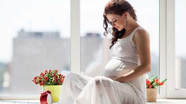 Беременная улыбается глядя на живот