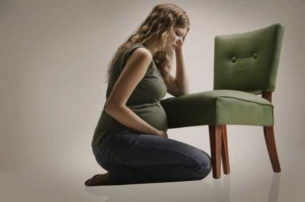 грустная беременная сидит на коленях, держась за голову