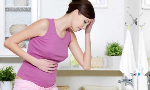 Беременная в первом триместре держится за голову и живот