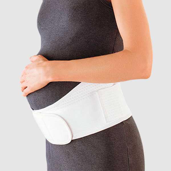 Беременная в поддерживающем бандаже поверх одежды