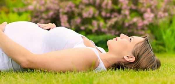 Беременная женщина лежит на траве