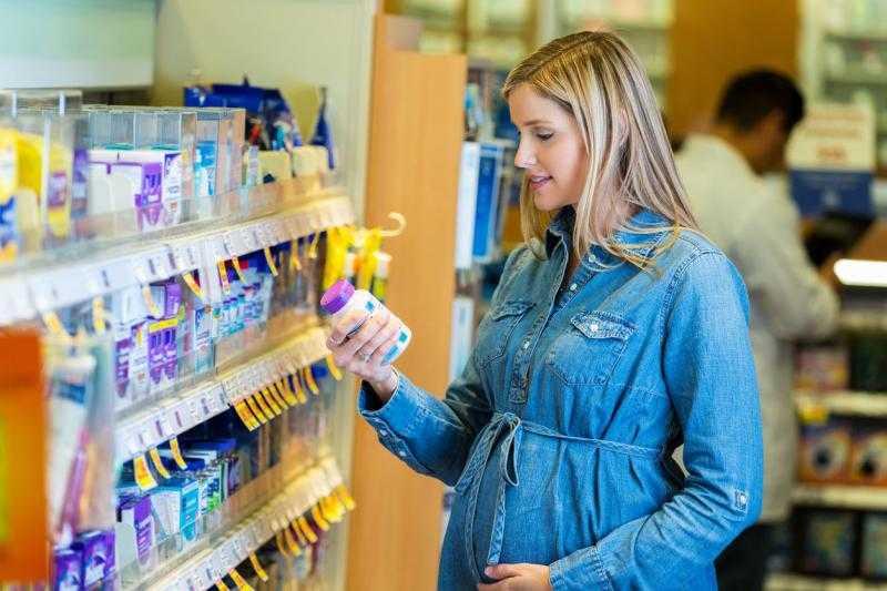 Беременная женщина держит флакон с лекарством в аптеке