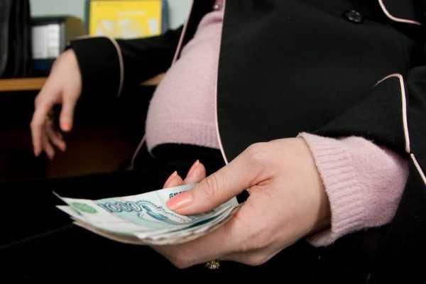 Беременная женщина держит в руке деньги