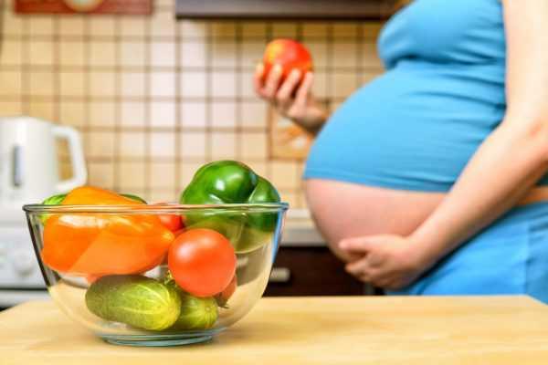 Овощи в прозрачной тарелке на столе, на заднем плане беременная женщина