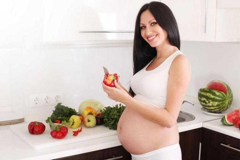 Беременная женщина готовит обед