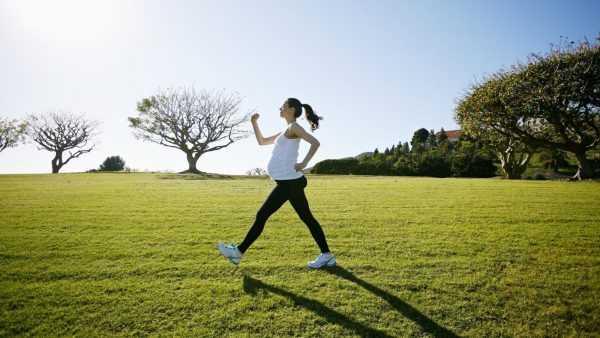 Беременная женщина идет по поляне