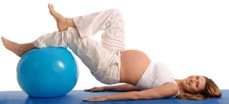 Беременная женщина лежит на спине, положив ноги на большой мяч