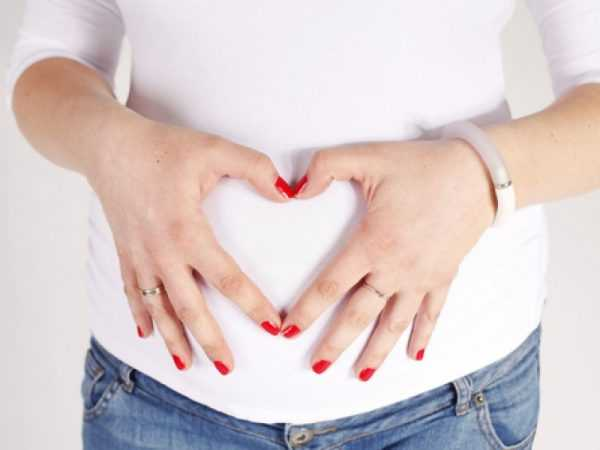 Живот беременной женщины, на котором она с помощью рук сложила сердце