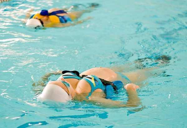 Беременные женщины плывут на спине в бассейне