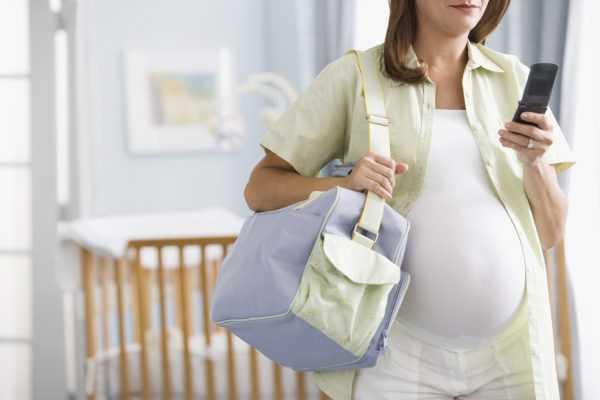 Беременная женщина с сумкой для роддома