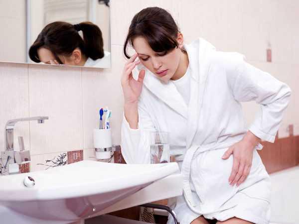 Беременная женщина сидит в ванной комнате перед раковиной, одной рукой держится за голову, второй за живот