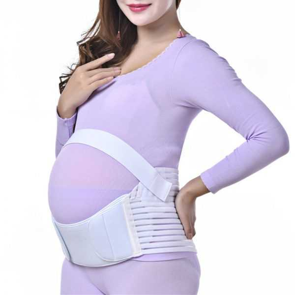 Беременная женщина в бандаже поверх одежды