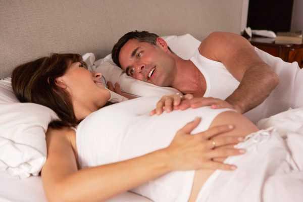Беременная женщина в постели с мужем
