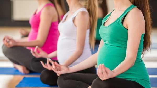 Беременные женщины сидят в позе лотоса