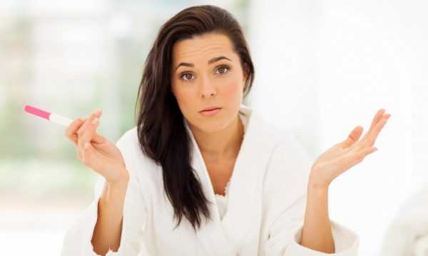 Женщина держит тест на беременнось