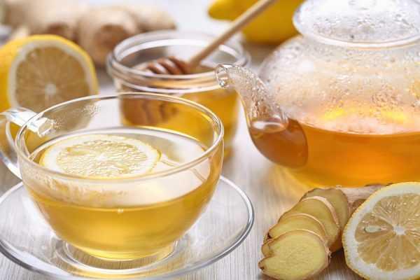 чай в чашке с долькой лимона, рядом банка мёда и кусочки имбиря