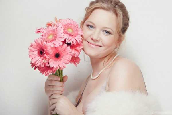 Девушка держит букет цветов и улыбается