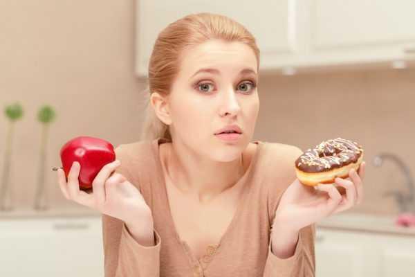 Девушка держит яблоко и пончик