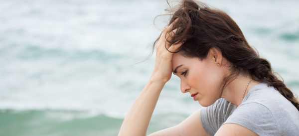 Девушка грустит на берегу моря