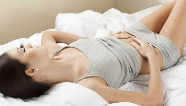 Девушка лежит на кровати и держится за живот